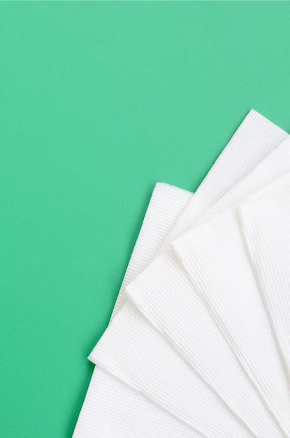 Einige weiße papierservietten liegen auf einem grünen plastikhintergrund Premium Fotos