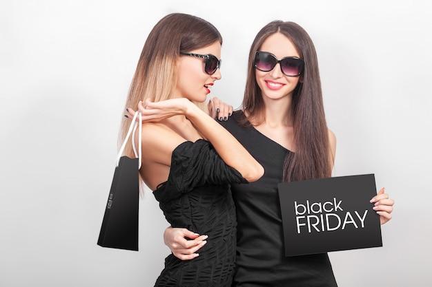 Einkaufen. zwei frauen, die schwarze taschen auf hellem hintergrund in schwarzem freitag-feiertag halten Premium Fotos