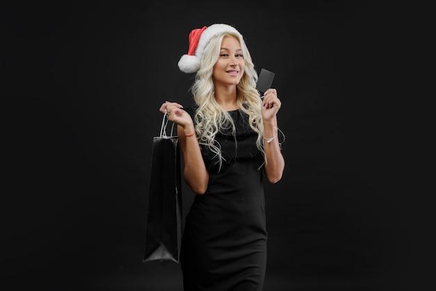Einkaufende frau in der weihnachtsmütze, die tasche ion dunkle wand in den weihnachtsferien hält. schwarzer freitag sale konzept Premium Fotos