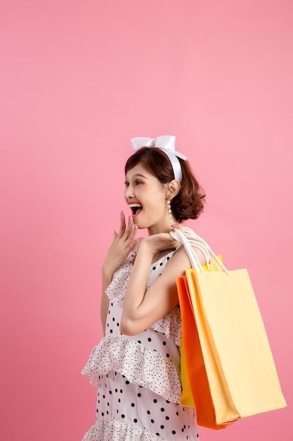 Einkaufsfrau, die einkaufstaschen auf rosa hält Kostenlose Fotos