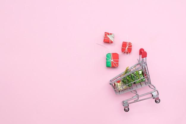 Einkaufslaufkatze auf einem rosa hintergrund mit geschenken, draufsicht. copyspace. geschäft, verkäufe, weihnachtseinkäufe. Premium Fotos