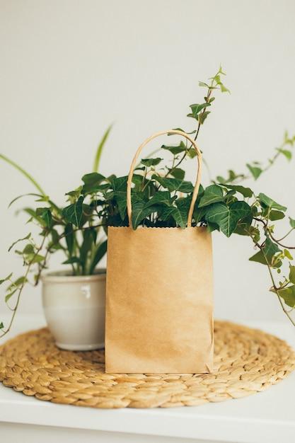 Einkaufstasche aus braunem und beigem papier mit efeu in modernem, hellem raum, Premium Fotos
