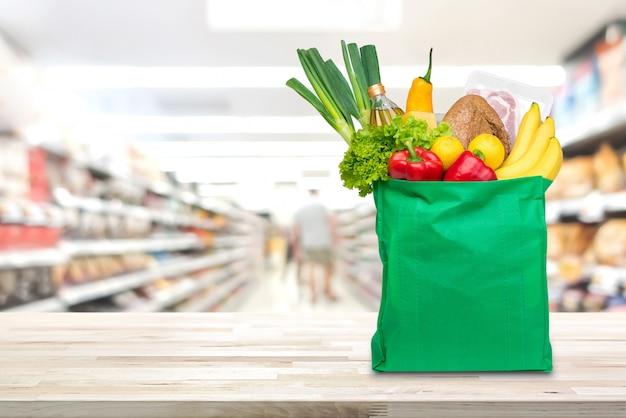 Einkaufstasche mit lebensmitteln und lebensmittelgeschäften auf dem tisch im supermarkt Premium Fotos