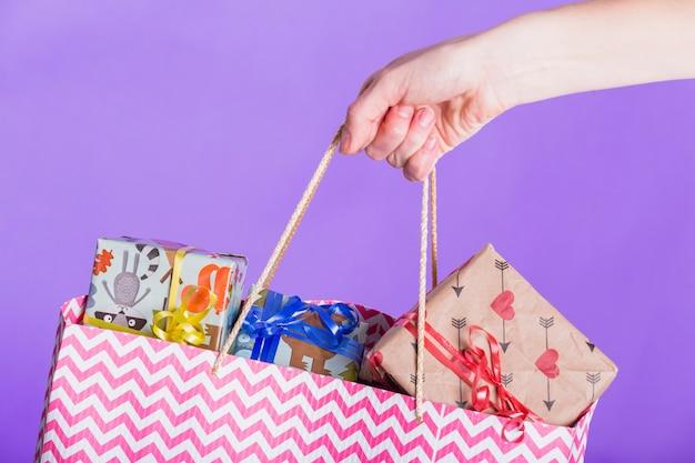 Einkaufstasche mit voll von eingewickeltem geschenk auf purpurrotem hintergrund Kostenlose Fotos