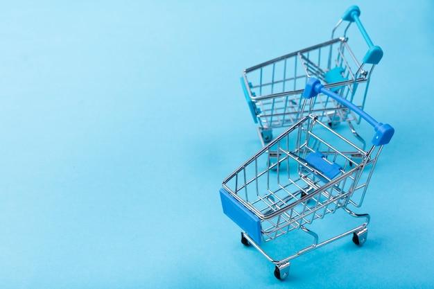Einkaufswagen auf blauem hintergrund mit kopieraum Kostenlose Fotos