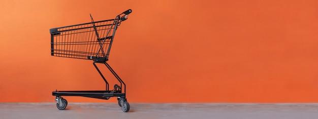 Einkaufswagen auf einem orangefarbenen hintergrund Premium Fotos