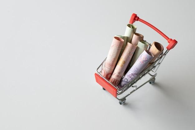 Einkaufswagen mit dem geld (thailändisches geld) auf weißem hintergrund Premium Fotos