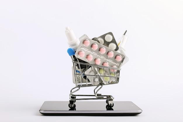 Einkaufswagen mit drogen und pillen ist auf dem smartphone. online-verkaufskonzept. Premium Fotos