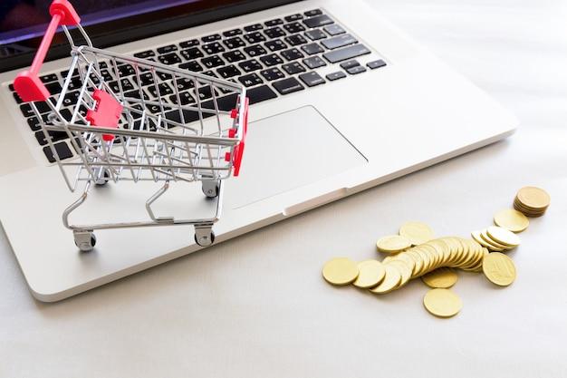 Einkaufswagen mit goldmünze und notizbuch. Premium Fotos