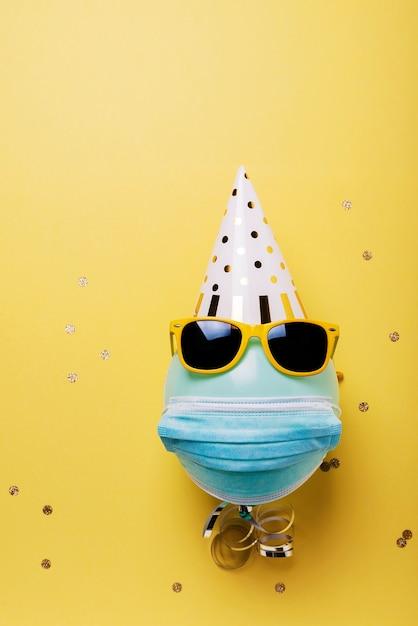 Einladungskarte mit blauem ballon mit schutzmaske, partyhut und sonnenbrille. Premium Fotos