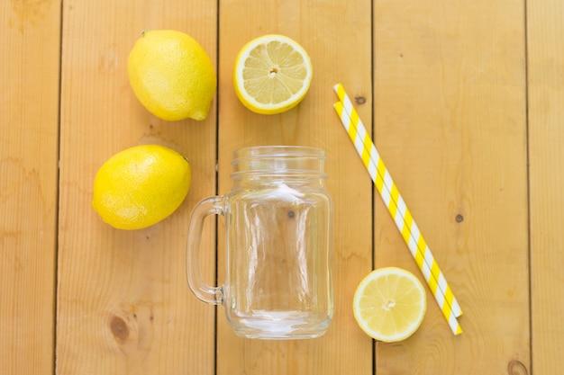Einmachglas, frische zitronen und strohe auf holztisch. flach liegen. bereit für einen cocktail. sommerferien urlaub. Premium Fotos