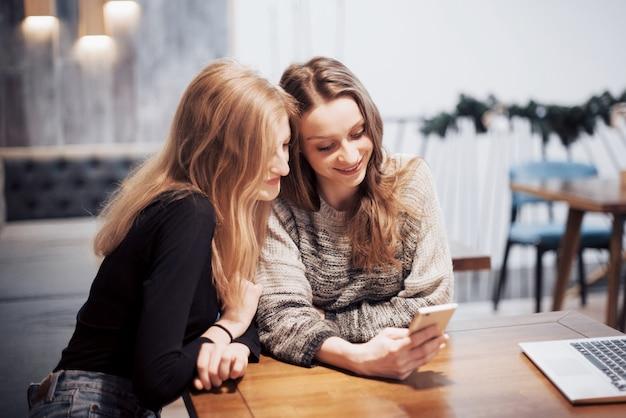 Eins-zu-eins-sitzung zwei junge geschäftsfrauen, die bei tisch im café sitzen mädchen zeigt ihr freundbild auf schirm von smartphone. auf dem tisch ist notebook geschlossen. freunde treffen Premium Fotos