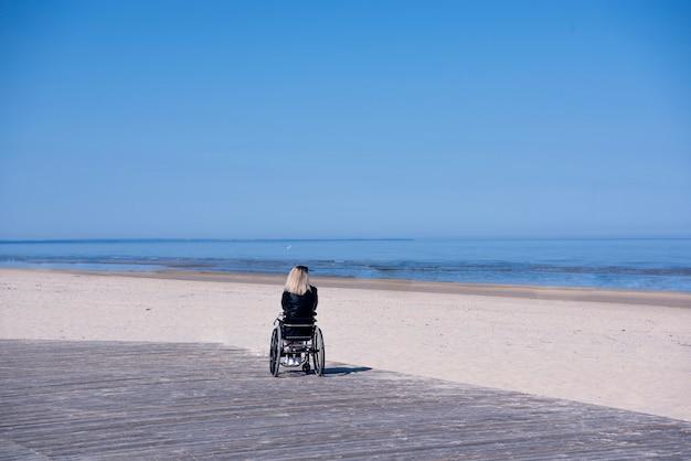 Einsame behinderte junge frau am strand. sonniger sommertag. Premium Fotos