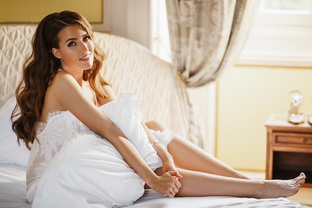 Einsame braut sitzt auf dem bett in einem großen hotelzimmer Kostenlose Fotos