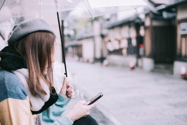 Einsame frau mit regenschirm wartet auf den regen auf der straße in japan. Premium Fotos