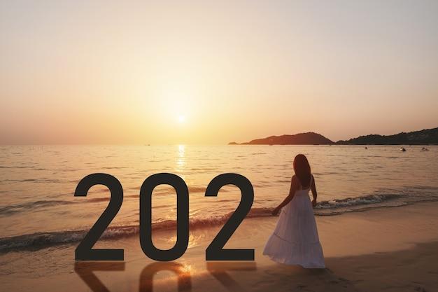 Einsame junge asiatische frau, die am strand bei sonnenuntergang mit neujahrskonzept 2021 steht Premium Fotos