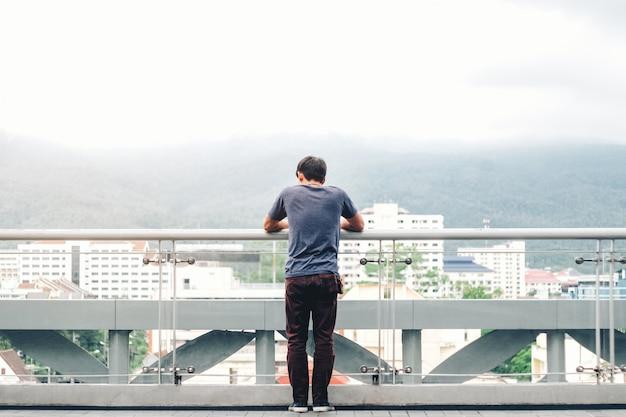 Einsame männer schauen auf die stadt und den sonnenuntergang Premium Fotos
