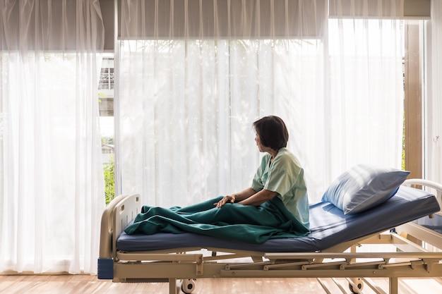 Einsamer älterer weiblicher patient, der auf bett am krankenhaus sitzt und weg außerhalb des fensters schaut, das wartet, um ihre familie zu sehen, um zu besuchen. Premium Fotos