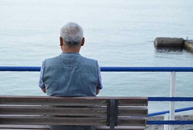 Einsamer grauhaariger älterer mann, der am meer auf einer bank sitzt, blick von hinten Premium Fotos