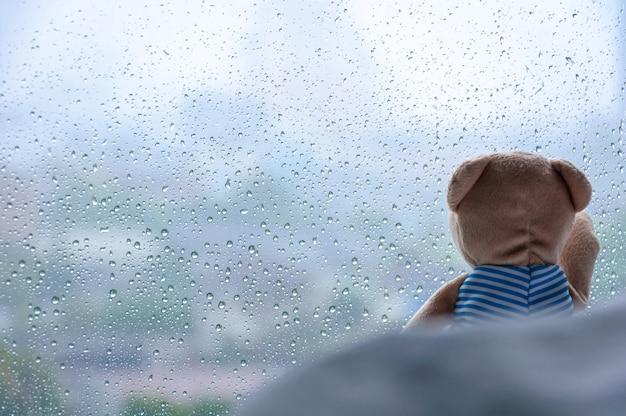 Einsamer teddy bear, der auf bett sitzt und heraus dem fenster am regnerischen tag betrachtet. Premium Fotos