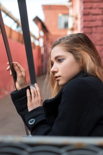 Einsames junges mädchen im schwarzen mantel, der auf treppe mit städtischem hintergrund der weinlese sitzt. einsamkeit. Premium Fotos