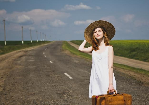 Einsames mädchen mit koffer an der landstraße Premium Fotos