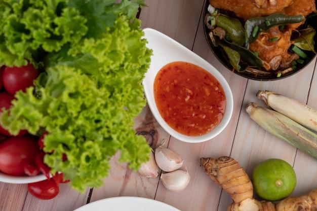 Eintauchen, zitronengras, knoblauch, limette, galangal, tomate und salat auf den holzboden Kostenlose Fotos