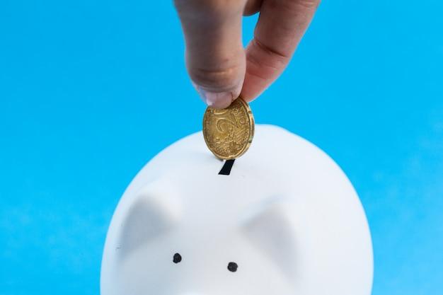 Einwurf einer münze in ein sparschwein Premium Fotos