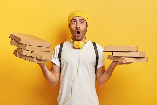 Einzelne aufnahme des überraschten lieferers hält mehrere kartons mit italienischer pizza in beiden händen, schockiert, um fast food an nicht korrekter stelle zu bringen, trägt weißes t-shirt, kopfhörer um den hals Kostenlose Fotos