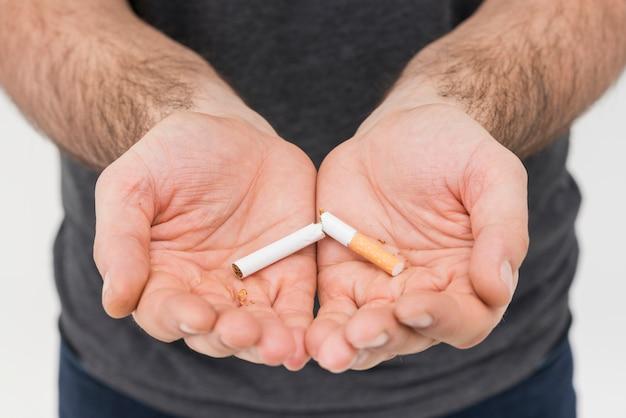 Einzelne gebrochene zigarette in der hand des mannes Kostenlose Fotos