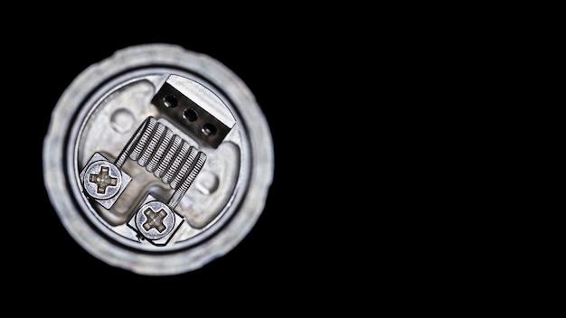 Einzelne geschmolzene clapton spule im wieder aufbaubaren behälterzerstäuber für den aromajäger lokalisiert auf schwarzem hintergrund Premium Fotos