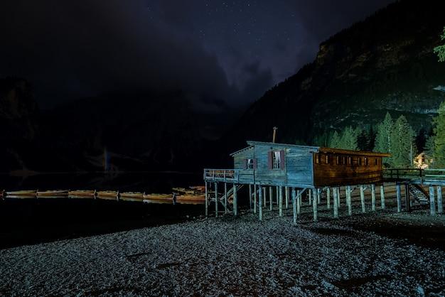 Einzelne holzhütte in der nähe von braies lake in italien, umgeben von hohen bergen in der nacht Kostenlose Fotos