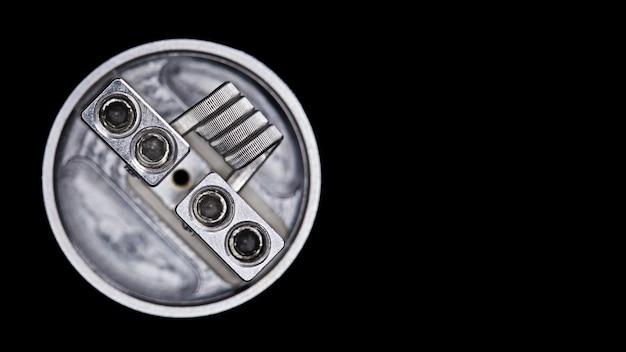 Einzelne verschmolzene clapton spule im wieder aufbaubaren tropfenden zerstäuber des unteren zufuhr-squonks für den aromajäger lokalisiert auf schwarzem hintergrund Premium Fotos