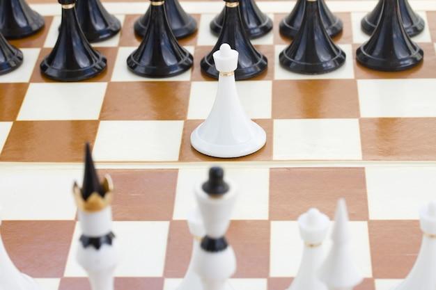 Einzelner weißer bauer vor schwarzem schach Premium Fotos
