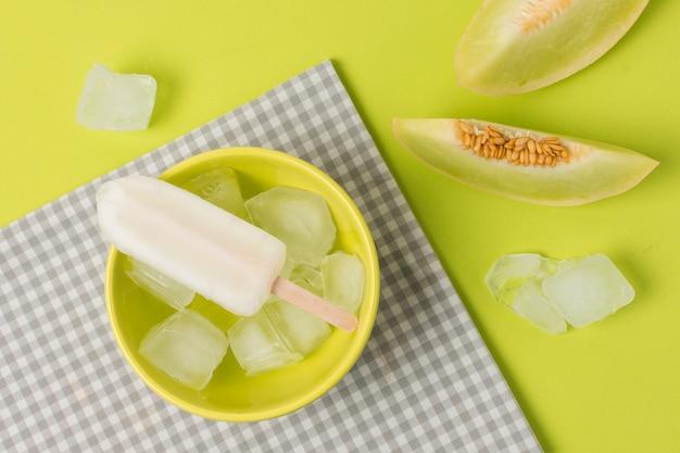 Eis am stiel in der schüssel nahe serviette und frischen früchten Kostenlose Fotos