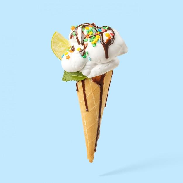Eiscreme in einem horn mit kalk-, minz- und schokoladenbelag auf einem blauen hintergrund. Premium Fotos