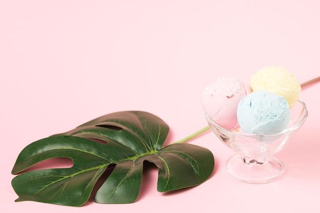 Eiscremebälle auf glasschüssel nahe monstera-blatt Kostenlose Fotos