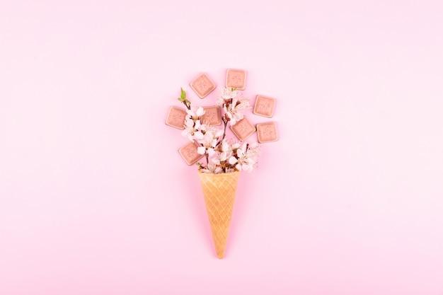 Eiscremewaffelkegel mit bunten blumen und rosa schokolade auf rosa Premium Fotos