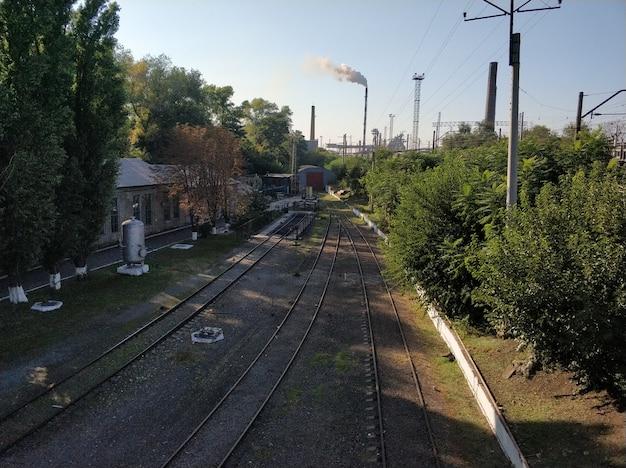 Eisenbahn. leere schienen mit rauchenden kaminen einer anlage Premium Fotos