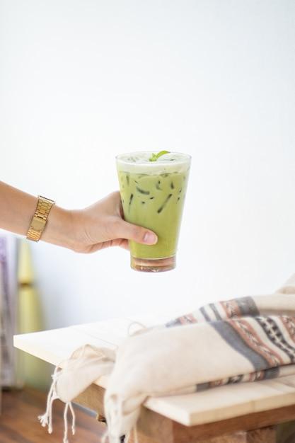 Eisgrüner tee oder matcha latte auf hohen gläsern mit stroh auf weißer hölzerner tabelle und kleidungsdekorationsgegenstand. Premium Fotos