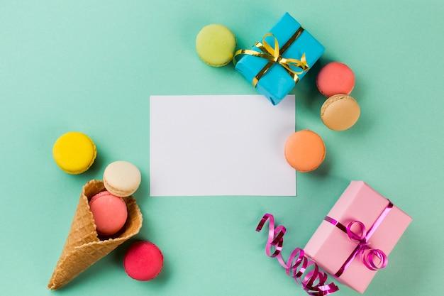 Eishörnchen; makronen; geschenkboxen nahe dem weißbuch auf tadellosem grünem hintergrund Kostenlose Fotos