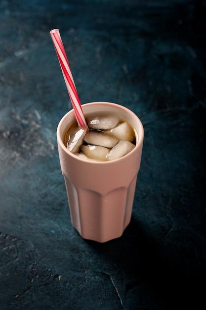 Eiskaffee in einem glas auf einer dunkelblauen steinoberfläche. konzeptkühlgetränk, durst, sommer, kolabaum mit eis. flach lag, ansicht von oben Premium Fotos