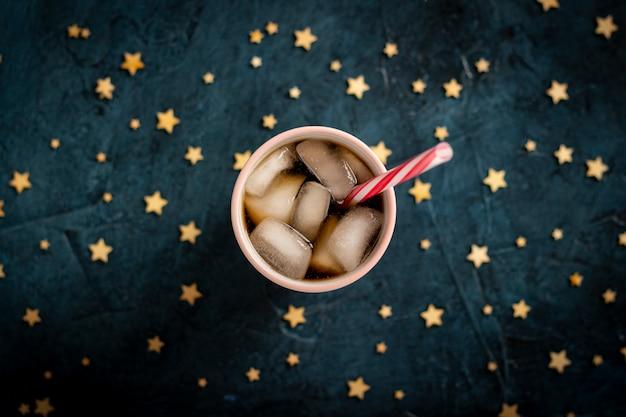 Eiskaffee in einem glas auf einer dunkelblauen steinoberfläche mit sternen. flachgelegt, draufsicht Premium Fotos