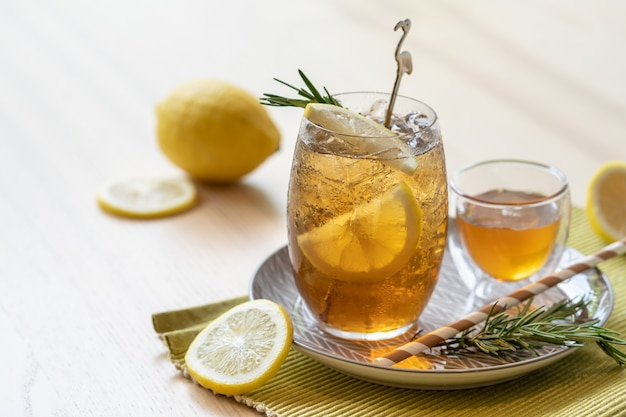 Eistee mit zitrone und honig auf platte, erfrischendes sommergetränk. Premium Fotos