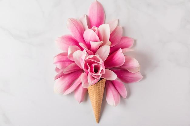Eistüte mit frühlingsrosa magnolienblütenzusammensetzung. minimales federkonzept. flach liegen Premium Fotos