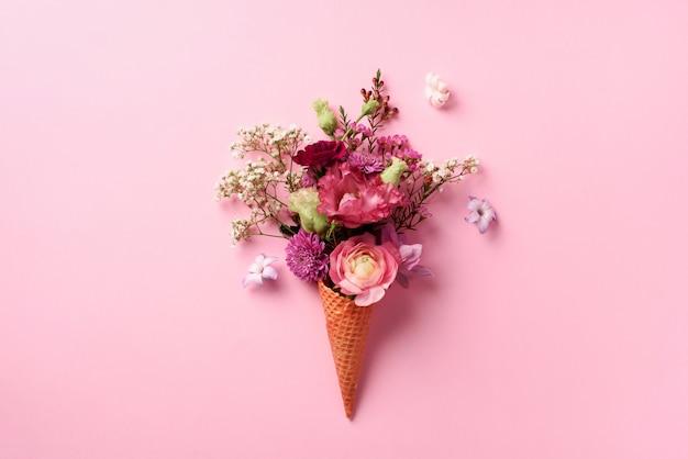 Eistüte mit rosa blumen und blättern auf schlagkräftigem pastellhintergrund. Premium Fotos