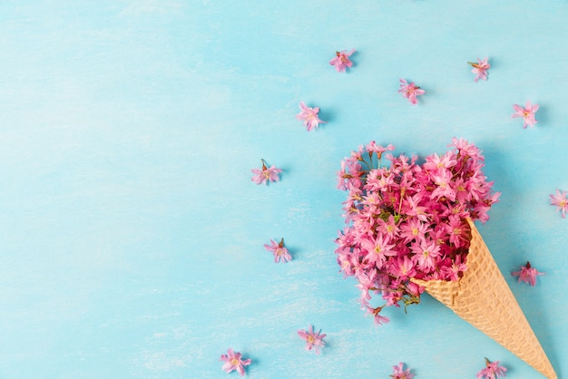 Eistüte mit rosa kirsch- oder sakura-blüten der frühlingsblüte mit kopierraum. flach liegen Premium Fotos