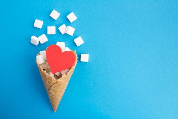 Eistüte mit rotem herzen und weißem zucker auf dem blauen hintergrund Premium Fotos