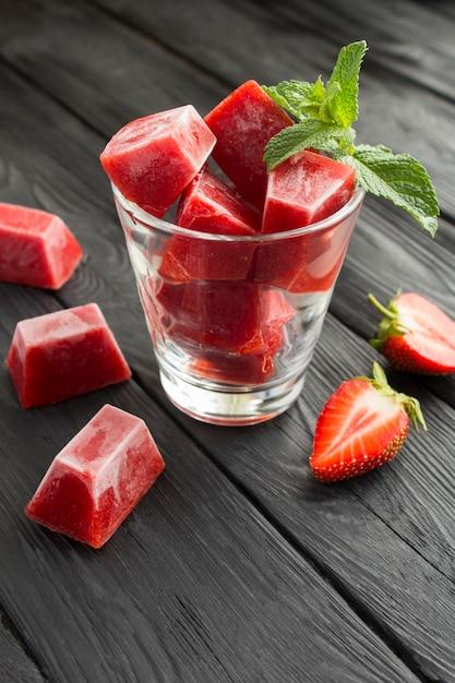 Eiswürfel mit erdbeere im glas auf der schwarzen holzoberfläche. lage vertikal. Premium Fotos