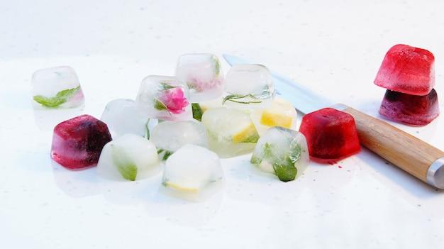 Eiswürfel mit minze, zitrone, rosmarin, thymian, beeren für cocktails und tee Premium Fotos